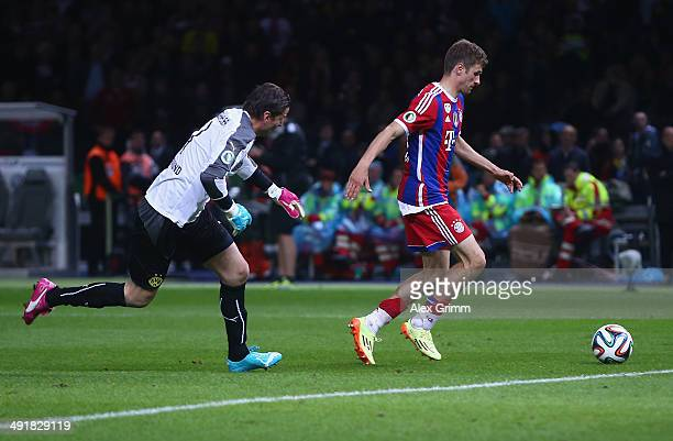 Thomas Mueller of Bayern Muenchen scores his team's second goal against goal keeper Roman Weidenfeller of Borussia Dortmund during the DFB Cup Final...