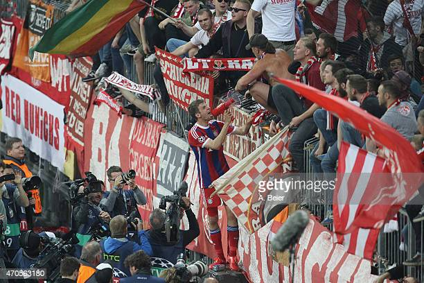 Thomas Mueller of Bayern Muenchen screams into a megaphone to celebrate his team's victory with the fans after the Champions League quarter final...