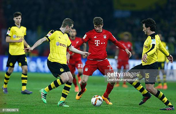 Thomas Mueller of Bayern Munich competes for the ball against Sven Bender and Mats Hummels of Borussia Dortmund during the Bundesliga match between...