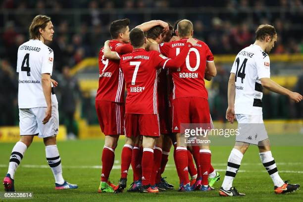 Thomas Mueller of Bayern Munich is congratulated by team mates after scoring a goal during the Bundesliga match between Borussia Moenchengladbach and...