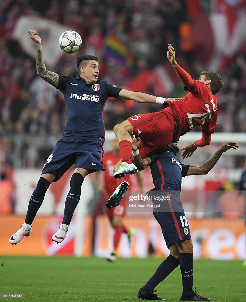 Thomas Mueller of Bayern Munich jumps with Jose Gimenez (24) and Augusto Fernandez of Atletico Madrid (12) during UEFA Champions League semi final second leg match between FC Bayern Muenchen and Club Atletico de Madrid at Allianz Arena on May 3, 2016 in Munich, Germany.
