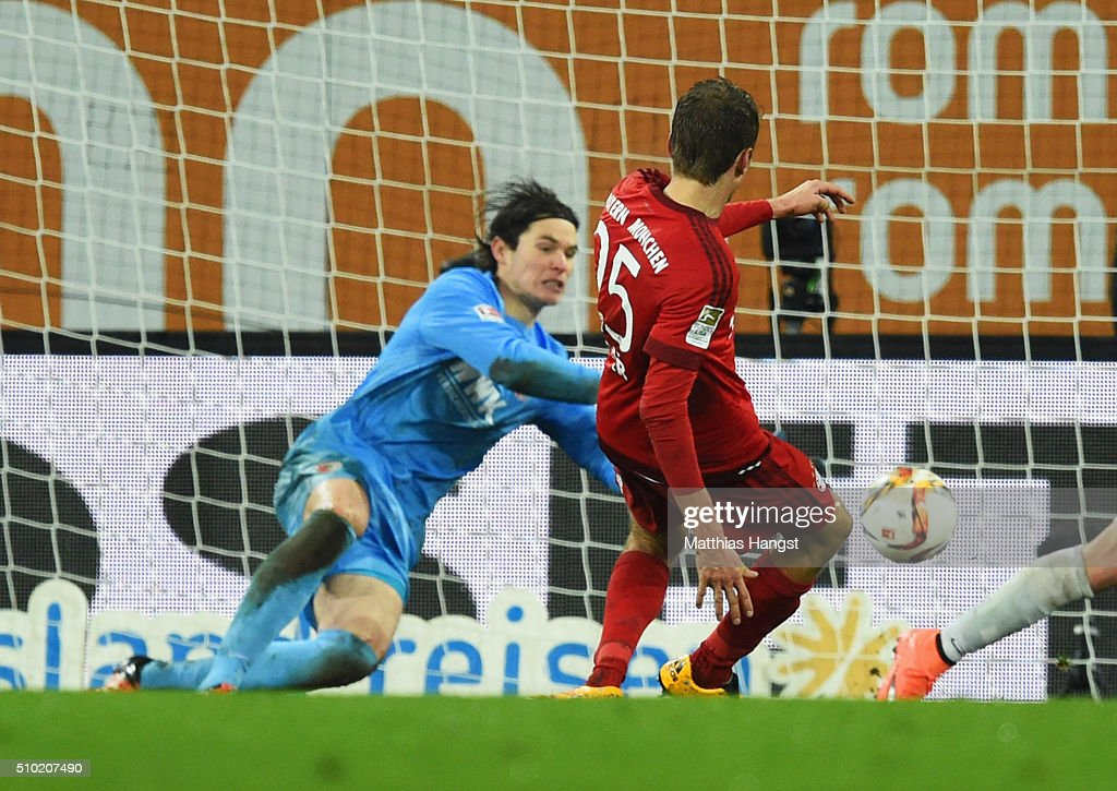 <a gi-track='captionPersonalityLinkClicked' href=/galleries/search?phrase=Thomas+Mueller&family=editorial&specificpeople=5842906 ng-click='$event.stopPropagation()'>Thomas Mueller</a> of Bayern Munich scores their third goal past <a gi-track='captionPersonalityLinkClicked' href=/galleries/search?phrase=Marwin+Hitz&family=editorial&specificpeople=5697209 ng-click='$event.stopPropagation()'>Marwin Hitz</a> of Augsburg during the Bundesliga match between FC Augsburg and FC Bayern Muenchen at SGL Arena on February 14, 2016 in Augsburg, Germany.