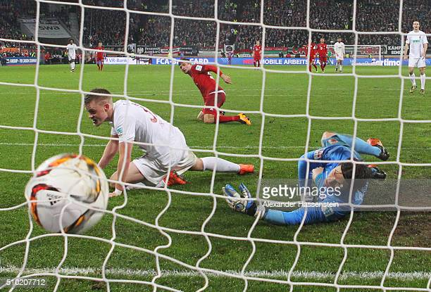 Thomas Mueller of Bayern Munich scores their third goal past goalkeeper Marwin Hitz of Augsburg during the Bundesliga match between FC Augsburg and...