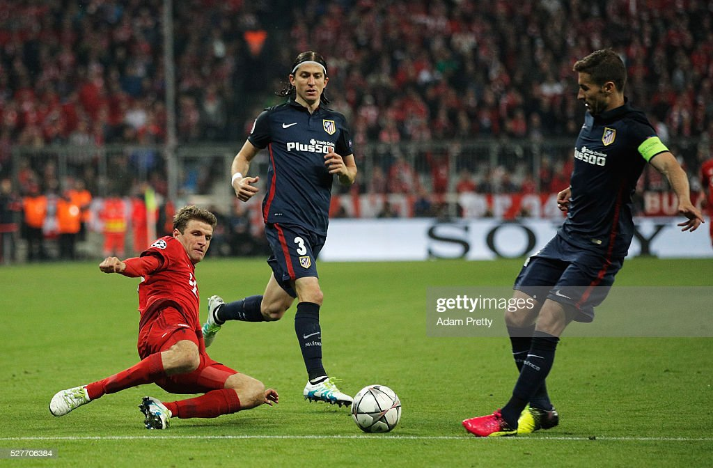 Thomas Mueller of Bayern Munich slides to tackle Gabi of Atletico Madrid during UEFA Champions League semi final second leg match between FC Bayern Muenchen and Club Atletico de Madrid at Allianz Arena on May 3, 2016 in Munich, Germany.