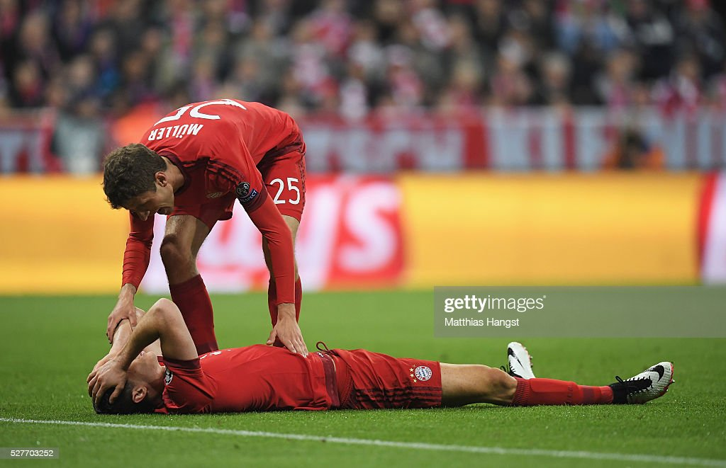 Thomas Mueller of Bayern Munich stands over injured team mate Robert Lewandowski during UEFA Champions League semi final second leg match between FC Bayern Muenchen and Club Atletico de Madrid at Allianz Arena on May 3, 2016 in Munich, Germany.