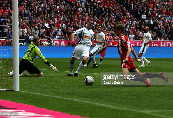 Thomas Mueller of Bayern scores the opening goal against goalkeeper Philipp Heerwagen of Bochum during the Bundesliga match between FC Bayern...