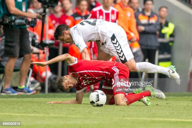 Thomas Mueller of FC Bayern Muenchen and Marc Oliver Kempf of SC Freiburg battle for the ball during the Bundesliga match between Bayern Muenchen and...