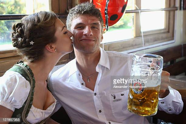 Thomas Mueller of FC Bayern Muenchen attends with his wife Lisa Mueller the Oktoberfest beer festival at the Kaefer Wiesnschaenke tent on October 2...