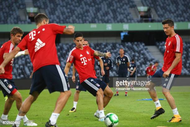 Thomas Mueller of FC Bayern Muenchen battle for the ball with his team mates Javier Martinez James Rodriquez and Robert Lewandowski during a training...