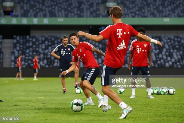 Thomas Mueller of FC Bayern Muenchen battles for the ball with his team mate James Rodriguez during a training session at Shenzhen Universiade Sports...