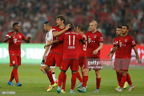 Thomas Mueller of FC Bayern Muenchen celebrates with teammates after scoring his second goal during the international friendly match between FC...