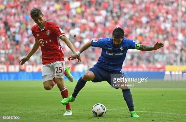 Thomas Mueller of FC Bayern Muenchen challenges Aytac Sulu of SV Darmstadt during the Bundesliga match between Bayern Muenchen and SV Darmstadt 98 at...