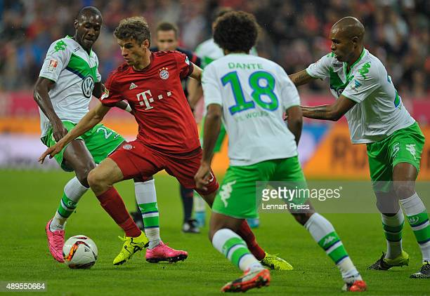 Thomas Mueller of FC Bayern Muenchen challenges Joshua Guilavogui Dante and Naldo of VfL Wolsburg during the Bundesliga match between FC Bayern...