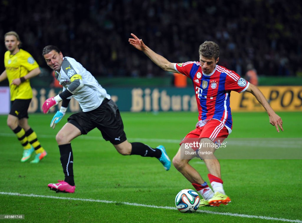 <a gi-track='captionPersonalityLinkClicked' href=/galleries/search?phrase=Thomas+Mueller&family=editorial&specificpeople=5842906 ng-click='$event.stopPropagation()'>Thomas Mueller</a> of FC Bayern Muenchen pus the ball past <a gi-track='captionPersonalityLinkClicked' href=/galleries/search?phrase=Roman+Weidenfeller&family=editorial&specificpeople=726753 ng-click='$event.stopPropagation()'>Roman Weidenfeller</a> of Dortmund as he scores the second goal during the DFB Pokal between FC Bayern Muenchen and Dortmund at Olympiastadion on May 17, 2014 in Berlin, Germany.