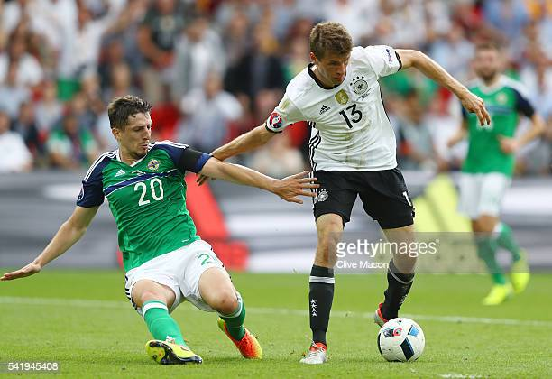 Thomas Mueller of Germany and Craig Cathcart of Northern Ireland compete for the ball during the UEFA EURO 2016 Group C match between Northern...