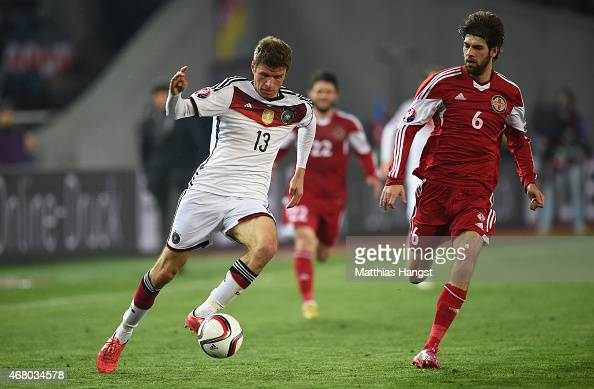 Thomas Mueller of Germany and Kakhi Makharadze of Georgia compete for the ball during the EURO 2016 Group D Qualifier match between Georgia and...