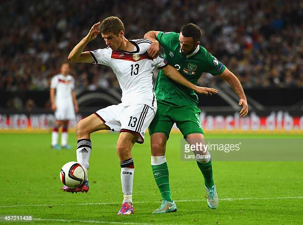 Thomas Mueller of Germany and Marc Wilson of the Republic of Ireland fight for the ball during the EURO 2016 Qualifier between Germany and Republic...