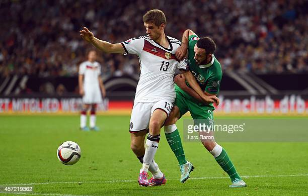 Thomas Mueller of Germany and Marc Wilson of the Republic of Ireland fight for the ball during the EURO 2016 Group D qualifying match between Germany...