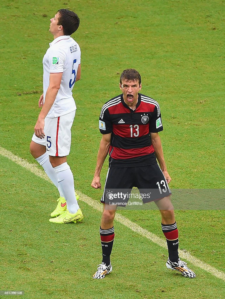 Thomas Mueller of Germany celebrates scoring his team's first goal as Matt Besler of the United States looks on during the 2014 FIFA World Cup Brazil group G match between the United States and Germany at Arena Pernambuco on June 26, 2014 in Recife, Brazil.