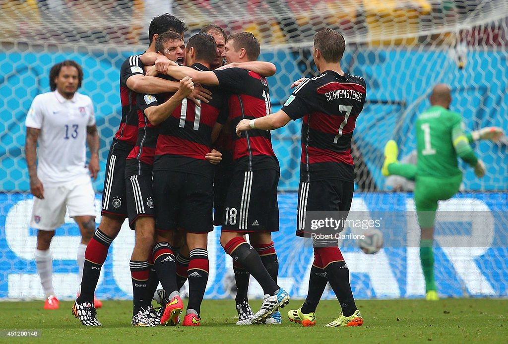 Thomas Mueller of Germany celebrates scoring his team's first goal with teammates as Jermaine Jones (L) and Tim Howard of the United States react during the 2014 FIFA World Cup Brazil group G match between the United States and Germany at Arena Pernambuco on June 26, 2014 in Recife, Brazil.
