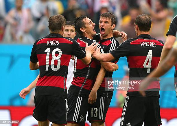 Thomas Mueller of Germany celebrates scoring his team's first goal with his teammates Benedikt Hoewedes Miroslav Klose and Toni Kroos during the 2014...
