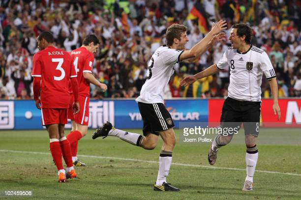 Thomas Mueller of Germany celebrates scoring his teams fourth goal with team mate Mesut Oezil during the 2010 FIFA World Cup South Africa Round of...