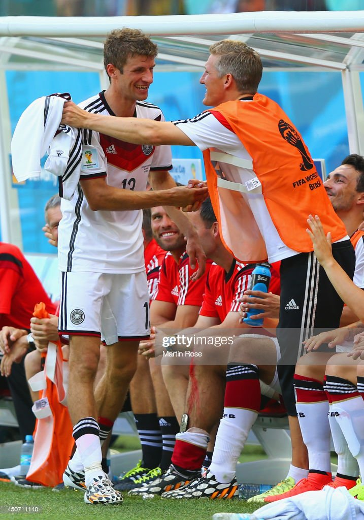 Thomas Mueller of Germany (L) celebrates with Bastian Schweinsteiger on the bench after scoring a hat trick and exiting the game during the 2014 FIFA World Cup Brazil Group G match between Germany and Portugal at Arena Fonte Nova on June 16, 2014 in Salvador, Brazil.