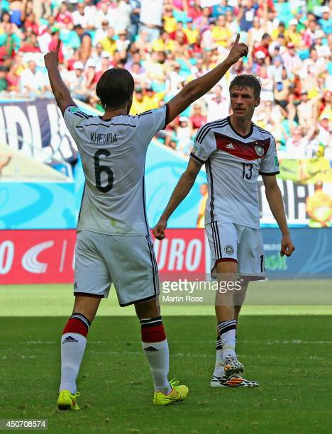 Thomas Mueller of Germany celebrates with teammate Sami Khedira after scoring his team's third goal during the 2014 FIFA World Cup Brazil Group G...