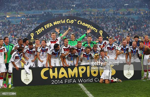 Thomas Mueller of Germany holds the World Cup trophy while celebrating with teammates after defeating Argentina 10 in extra time during the 2014 FIFA...