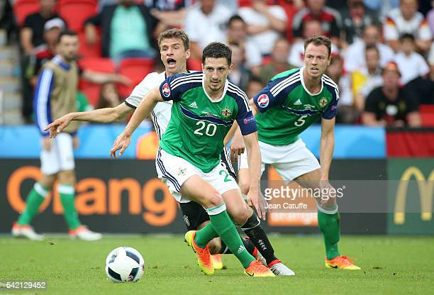 Thomas Mueller of Germany in action between Craig Cathcart and Jonny Evans of Northern Ireland during the UEFA EURO 2016 Group C match between...