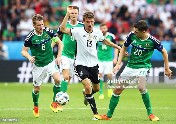 Thomas Mueller of Germany is challenegd by Steven Davis and Craig Cathcart of Northern Ireland during the UEFA EURO 2016 Group C match between...