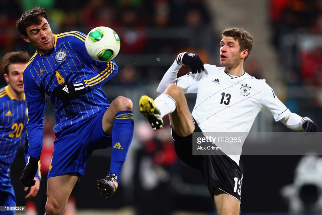 Thomas Mueller (R) of Germany is challenged by Moukhtar Moukhtarov of Kazakhstan during the FIFA 2014 World Cup qualifier between Germany and Kazakhstan at Grundig-Stadion on March 26, 2013 in Nuremberg, Germany.