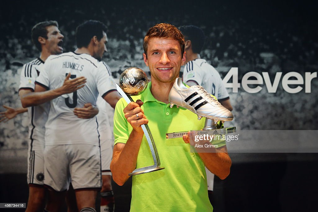 Thomas Mueller of Germany poses the adidas Silver Ball and adidas Silver Shoe awards during his visit at the adidas headquarters on October 6, 2014 in Herzogenaurach, Germany.