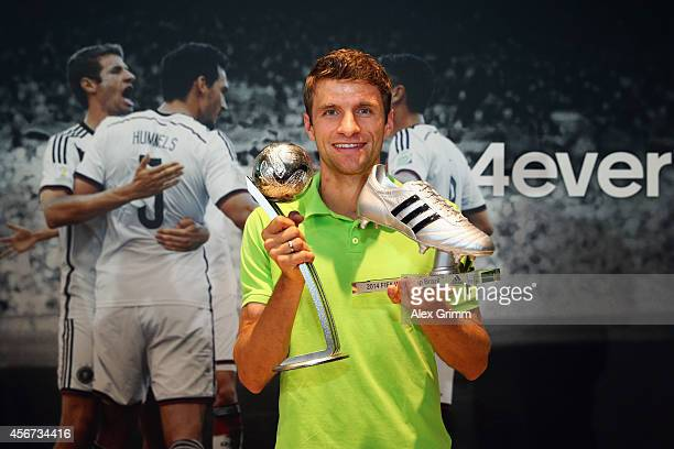Thomas Mueller of Germany poses the adidas Silver Ball and adidas Silver Shoe awards during his visit at the adidas headquarters on October 6 2014 in...