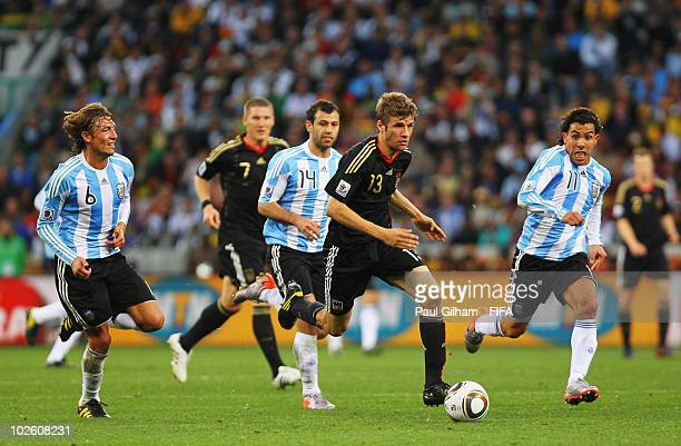 Thomas Mueller of Germany runs with ball from Gabriel Heinze Javier Mascherano and Carlos Tevez of Argentina during the 2010 FIFA World Cup South...
