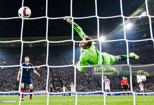 Thomas Mueller of Germany scores his team's first goal against goalkeeper David Marshall of Scotland during the EURO 2016 Qualifier match between...
