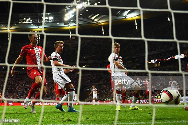 Thomas Mueller of Germany scores the opening goal during the EURO 2016 Qualifier Group D match between Germany and Poland at CommerzbankArena on...