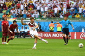 Thomas Mueller of Germany shoots and scores his team's first goal on a penalty kick during the 2014 FIFA World Cup Brazil Group G match between...