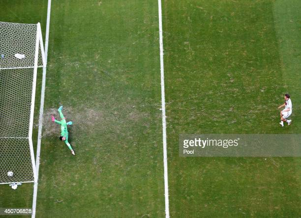 Thomas Mueller of Germany shoots and scores his team's first goal on a penalty kick past Rui Patricio of Portugal during the 2014 FIFA World Cup...
