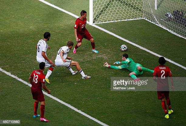 Thomas Mueller of Germany shoots and scores his team's fourth goal and completes his hat trick past Rui Patricio of Portugal during the 2014 FIFA...