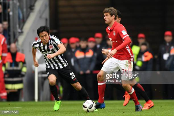 Thomas Mueller of Muenchen and Makoto Hasebe of Frankfurt compete for the ball during the Bundesliga match between Bayern Muenchen and Eintracht...
