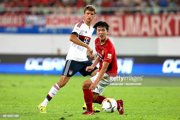 Thomas Mueller of Muenchen battles for the ball with Kim Young Gwon of Guangzhou during the international friendly match between FC Guangzhou...