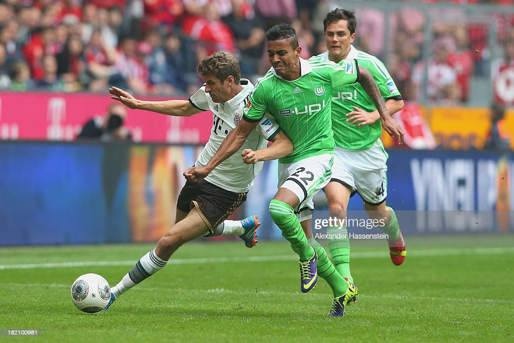 Thomas Mueller of Muenchen battles for the ball with Luiz Gustavo of Wolfsburg during the Bundesliga match between FC Bayern Muenchen and VfL...