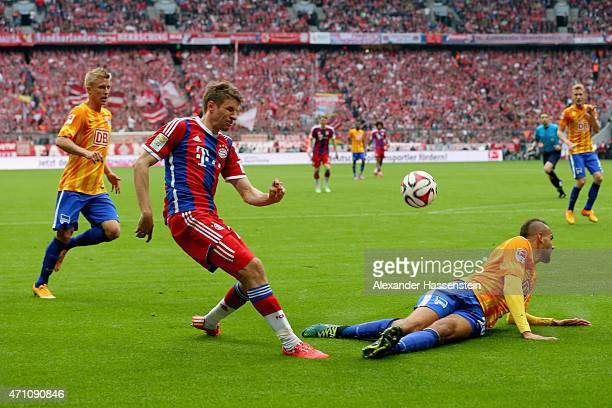 Thomas Mueller of Muenchen battles for the ball with Per Ciljian Skjelbred of Berlin and his team mate John Anthony Brooks during the Bundesliga...