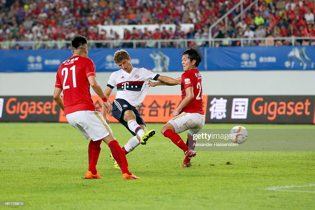 <a gi-track='captionPersonalityLinkClicked' href=/galleries/search?phrase=Thomas+Mueller&family=editorial&specificpeople=5842906 ng-click='$event.stopPropagation()'>Thomas Mueller</a> of Muenchen battles for the ball with Xuri Zhao (L) of Guangzhou and his team mate Kim Young Gwon during the international friendly match between FC Guangzhou Evergrande Taobao FC and FC Bayern Muenchen of the Volkswagen Cup Guangzhou at Tianhe Stadium on July 23, 2015 in Guangzhou, China.