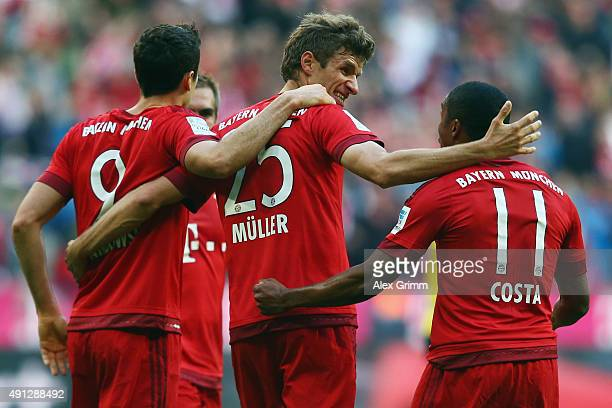 Thomas Mueller of Muenchen celebrates his team's first goal with team mates Robert Lewandowski and Douglas Costa during the Bundesliga match between...