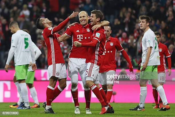 Thomas Mueller of Muenchen celebrates his team's fourth goal with team mates Thiago Alcantara and Arjen Robben during the Bundesliga match between...