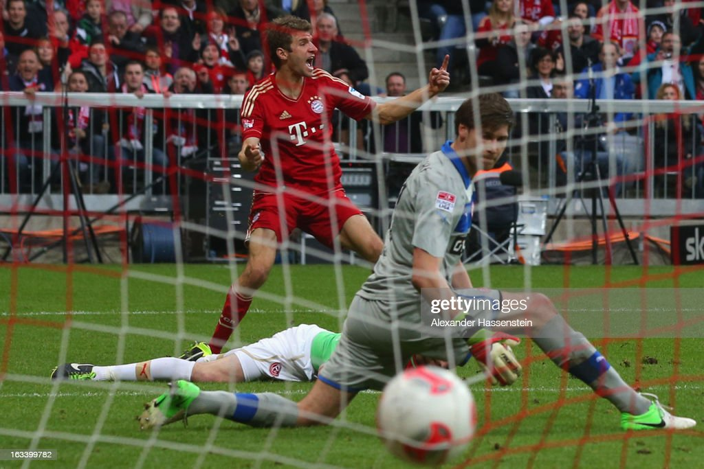 Thomas Mueller (L) of Muenchen celebrates scoring the first team goal against Fabian Giefer, keeper of Duesseldorf during the Bundesliga match between FC Bayern Muenchen and Fortuna Duesseldorf 1895 at Allianz Arena on March 9, 2013 in Munich, Germany.