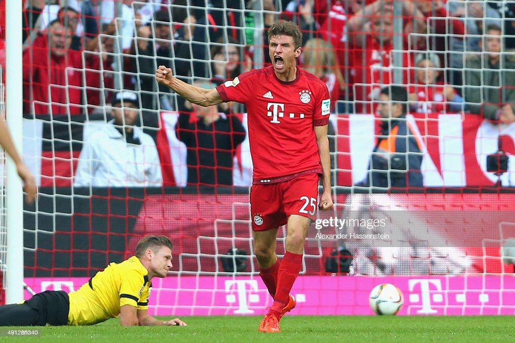 Thomas Mueller of Muenchen celebrates scoring the opening goal whilst Lukasz Piszczek of Dortmund looks dejected during the Bundesliga match between...