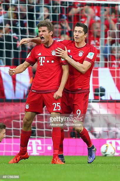 Thomas Mueller of Muenchen celebrates scoring the opening goal with his team mate Robert Lewandowski during the Bundesliga match between FC Bayern...